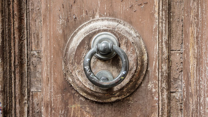 Close-up of an old handle on a brown wooden door