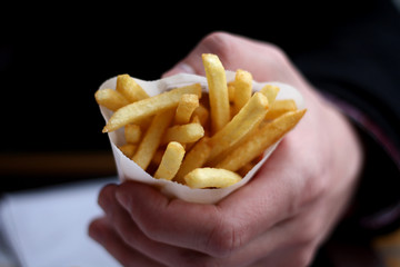 Hand holding small portion of French fries.