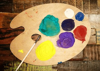 Wooden art palette with paint and brush on vintage background