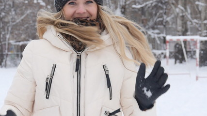 Happy girl in the hat throws snow in winter