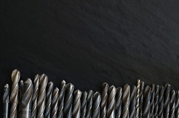 Set of old, worn drill bits on a dark table
