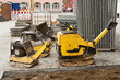 Drei gelbe Sandrüttler und verschiedene Baustellen-Utensilien
