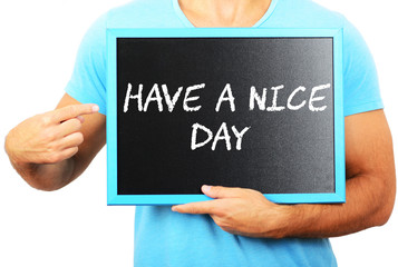 Man holding blackboard in hands and pointing the word HAVE A NIC