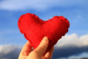 Red heart in woman's hand with blue sky in background