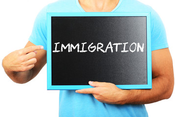 Man holding blackboard in hands and pointing the word IMMIGRATIO