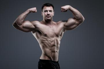 Handsome bodybuilder posing in the studio