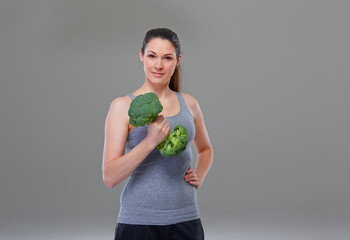 Young woman making arm exercise with broccoli, symbol