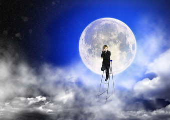 Boy in suit stands on a step-ladder against the background of a