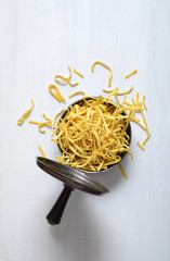 Raw, uncooked pasta in a metal pot with a lid