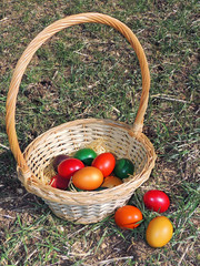 Basket With Colorful Easter Eggs On The Ground