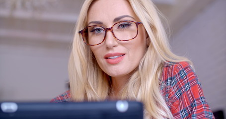 Blond Woman with Glasses Busy with Tablet Computer