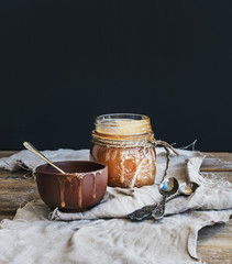 Salted caramel sauce in a rustic glass jar and brown ceramic cup