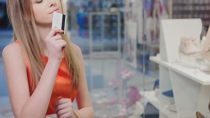 Woman with shopping bags at the wind holding credit card and