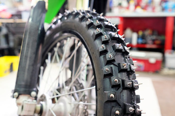 Closeup detail of a motorcycle front wheel with metall spikes