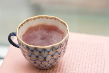 Tea in a vintage cup on a pink book. Selective focus.