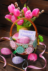 wicker basket with easter eggs and bunch of tulips