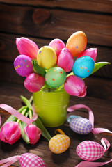 bunch of pink tulips and colorful easter eggs