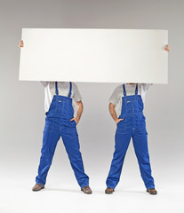 Two builders holding a banner