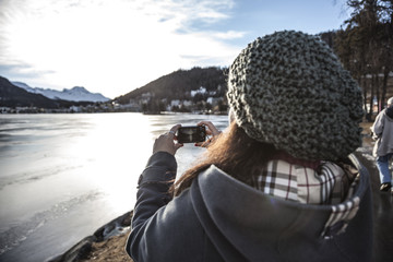 Woman takes a picture of a frozen lake