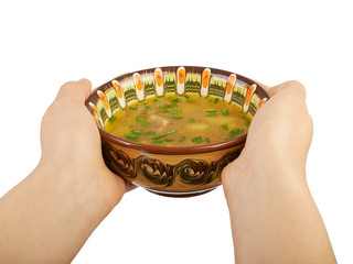 Ceramic bowl of soup in the hands isolated on white background