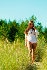 woman walking on grassy dune