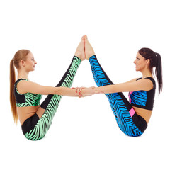 Pretty gymnasts posing in pair, isolated on white