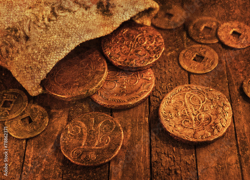 Leinwandbild Motiv Ancient coins on wooden background with texture effect