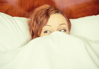Young shy woman lying in bed hiding under duvet blanket