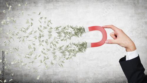 Leinwanddruck Bild hand attracts money