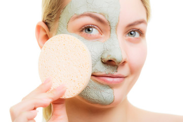 Skin care. Woman removing green clay mud facial mask with sponge
