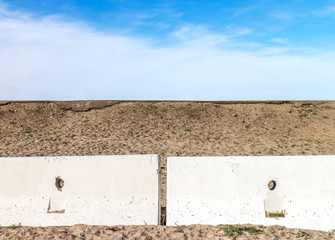 Concrete barrier in front of a sand hill blue sky and clouds
