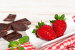 Red ripe strawberry and pieces of chocolate