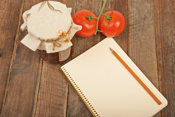 Conservation, tomato and notebook with pencil wooden background