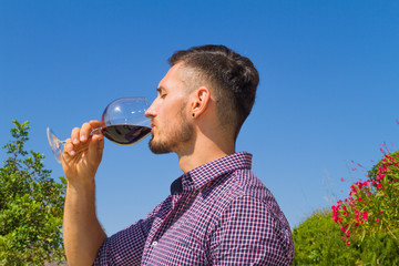 Young farmer tastes a glass of red wine