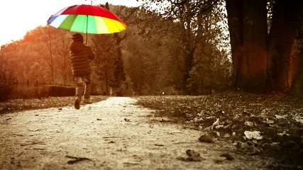 Bright warm-toned footage: merry little boy jumps with umbrella