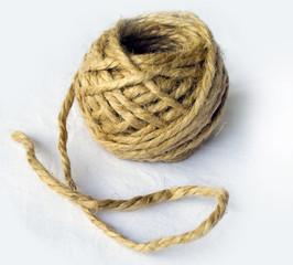 Rollo / madeja / ovillo de cáñamo crudo sobre fondo blanco