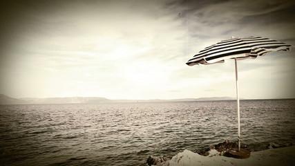 Lonely retro style umbrella on the mediterranean croatian shore