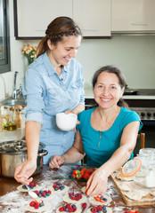 Two smiling women making  vareniki with berries