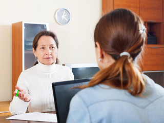 Senior woman answer questions of social worker