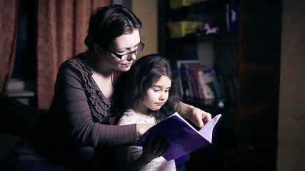 Mom with glasses  woman and her daughter do homework teen girl