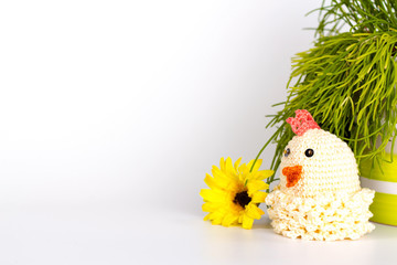knitted toy - chicken on a grass background