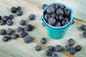 Blueberries in  small buckets on  wooden table.