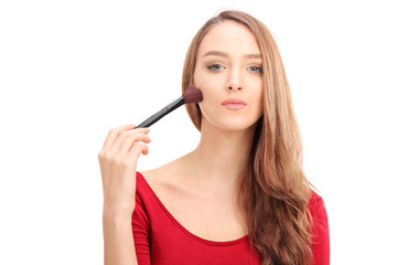 Gorgeous woman applying make-up with a brush