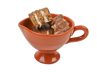 Pieces of chocolate sponge cake in a ceramic bowl isolated on wh