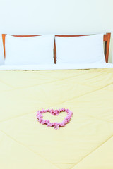 Heart from Cherry blossoms or sakura on the bed