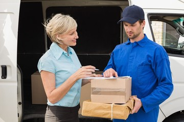 Delivery driver showing where to sign to customer