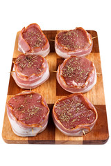 Steak with bacon and spices prepared for grilling. Isolated