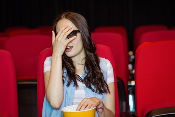 Young woman watching a scary 3d film