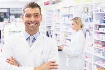 Smiling pharmacist standing with arms crossed