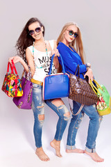 Two fashion girls and many different shopping bags in hands
